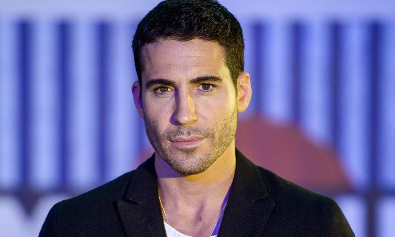 Everyone is saying Adam Sandler, but all I'm seeing is Lito from the TV series Sense8. Lito is played by Miguel Ángel Silvestre.  Miguel with another dog.