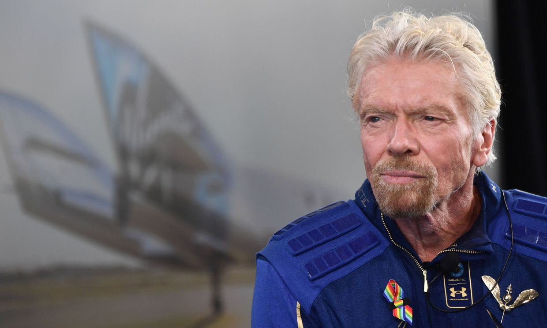 Richard Brandson con aspecto serie, detras de el podemos ver el avión usado por Virgin Galactic para sus vuelos