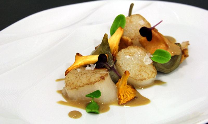 Vieiras, alcachofas confitadas, rebozuelos y salsa de 'foie gras'