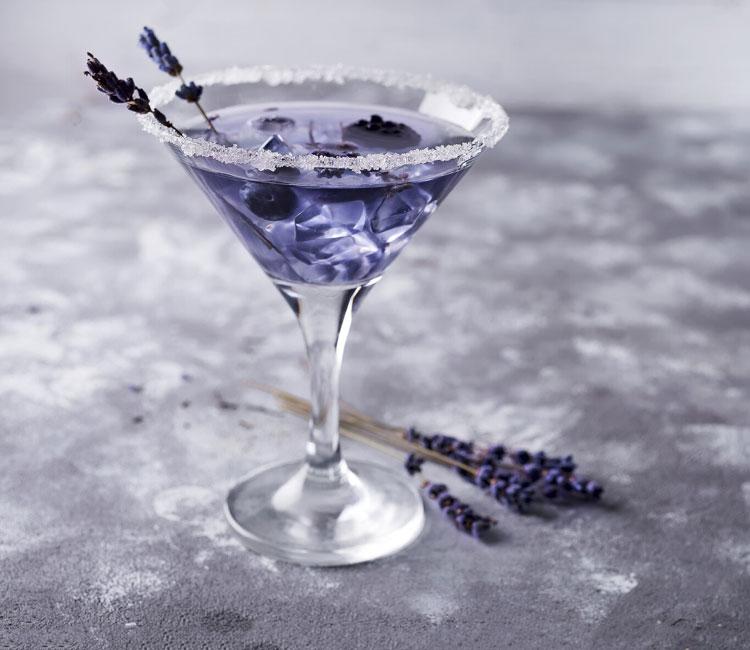 Cóctel de martini blanco con violeta y arándanos