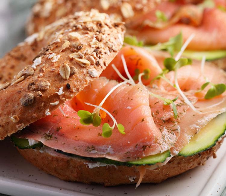 Bagel de semillas con salmón ahumado, queso crema y pepino