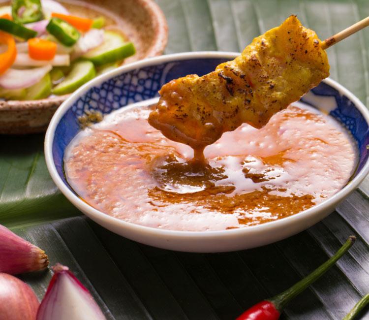 Brochetas de cerdo con salsa satay de plátano