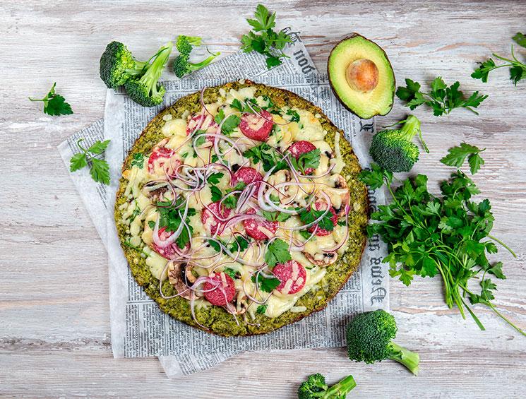 Pizza con base de brócoli con mozarela, cebolla morada, salami y champiñones