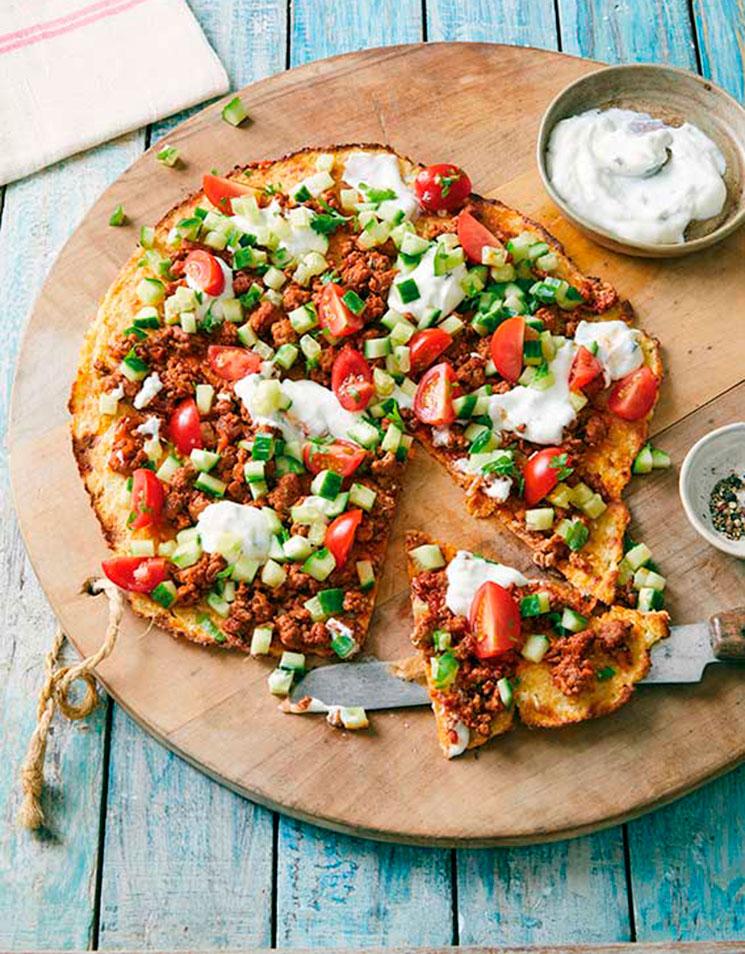 Pizza con base de plátano con carne adobada, pepino, tomate y ricotta