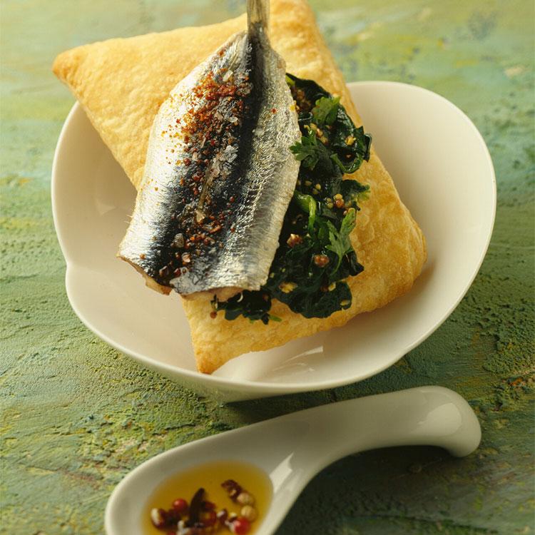 Aperitivo de sardinas sobre mojo verde y aceite picante