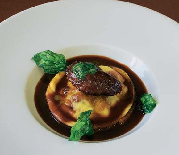 Raviolis de carrillera de cerdo braseada al vino tinto sobre fondue de tomate con albahaca