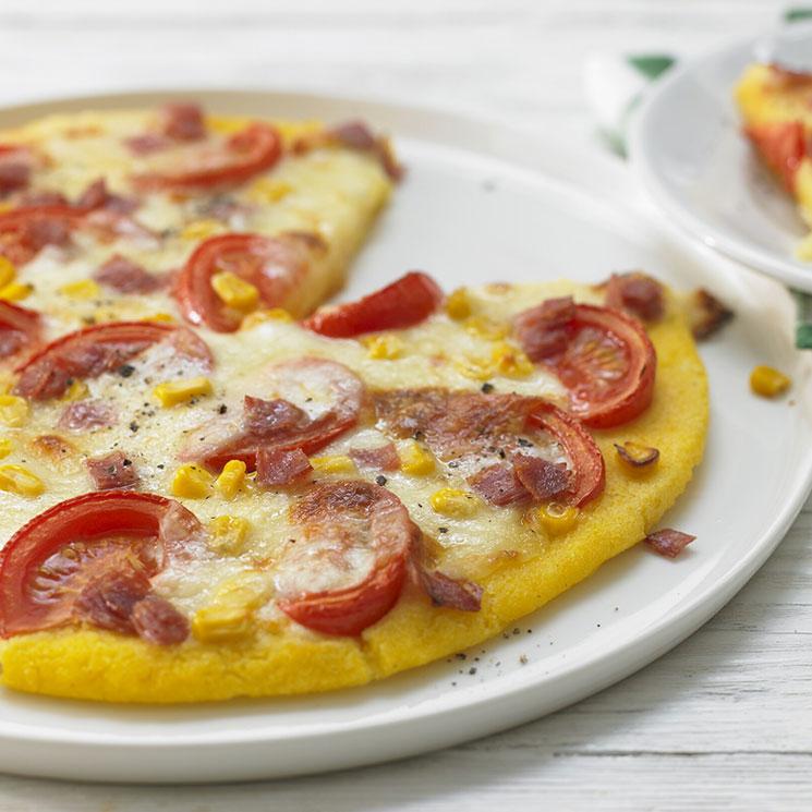 Pizza con base de polenta con salami, maíz y tomate