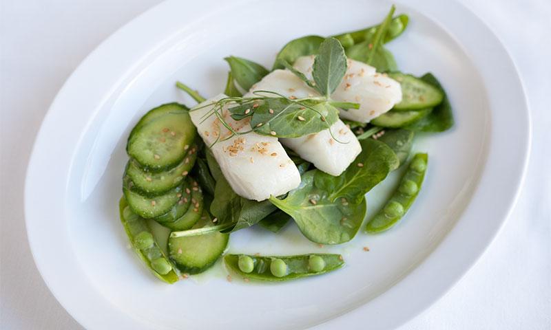 Ensalada de bacalao, pepino, guisantes y hojas verdes