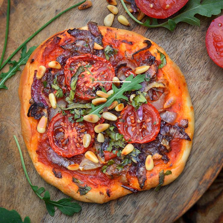 Pizza de tomate, cebolla y piñones