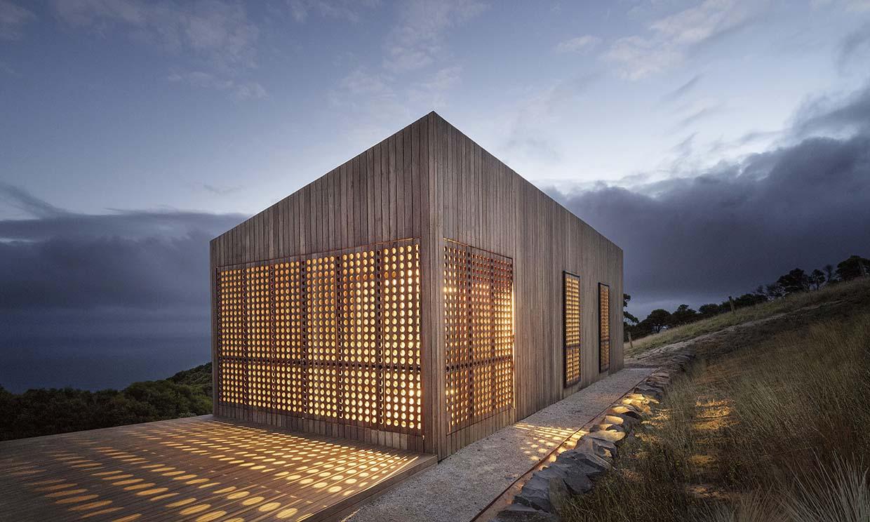 Una casa de madera bajo las estrellas concebida como una caja de luz