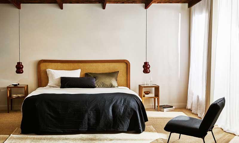 Dormitorio de matrimonio con cama con cabecero de rejilla y funda nórdica de color negro