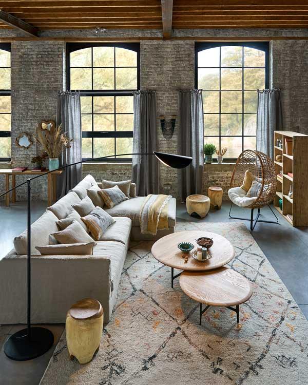 Salón con sofá con chaise longue, sillón 'huevo' de fibras vegetales y alfombra con motivos étnicos