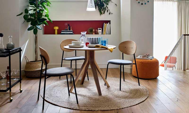 Comedor con mesa redonda de madera y alfombra y cestos de fibras vegetales
