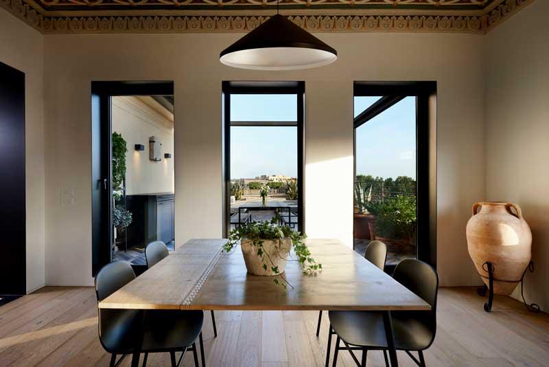 Comedor en madera y negro delante de ventanal