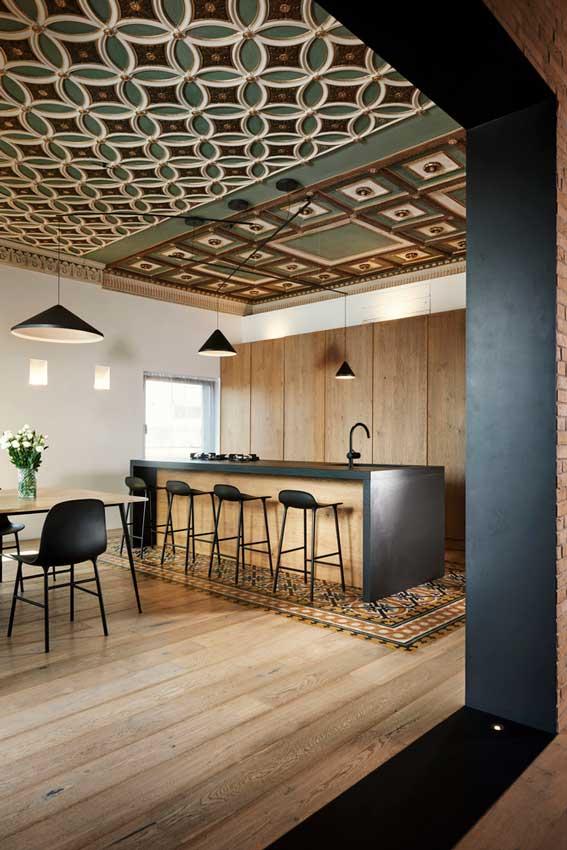Cocina moderna abierta con isla y techos de madera restaurados