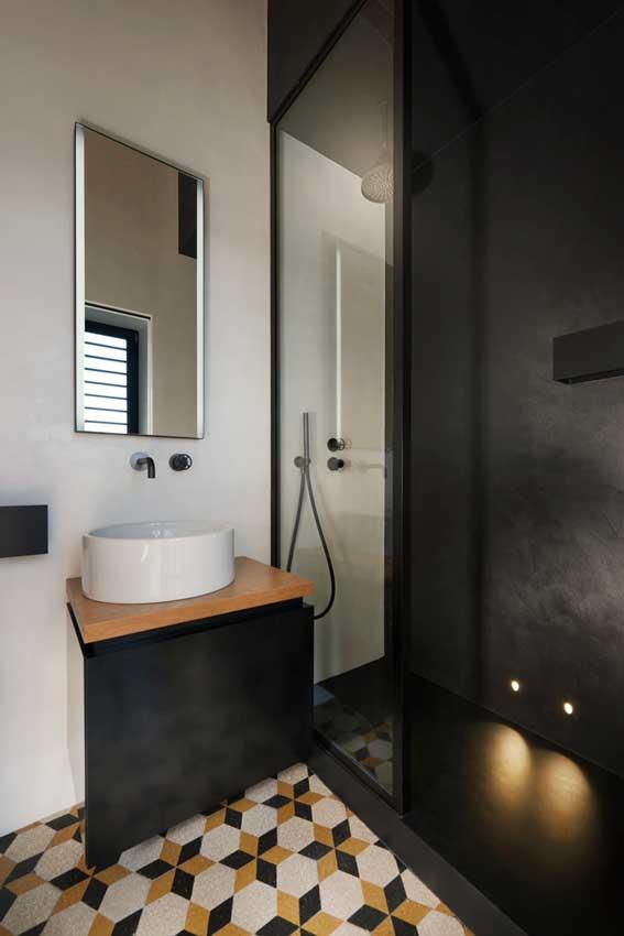 Baño decorado en negro con suelo hidráulico