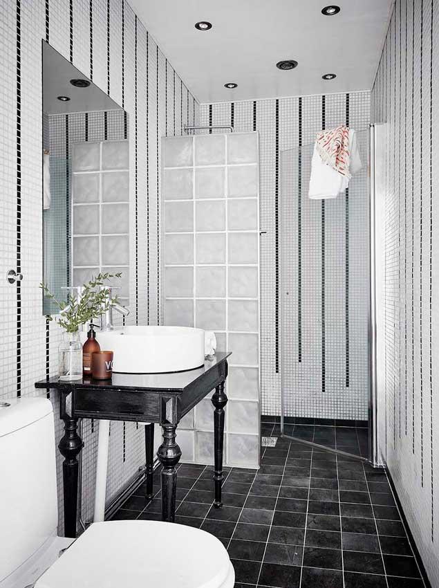 Baño de inspiración nórdica con ducha y mueble antiguo en el lavabo