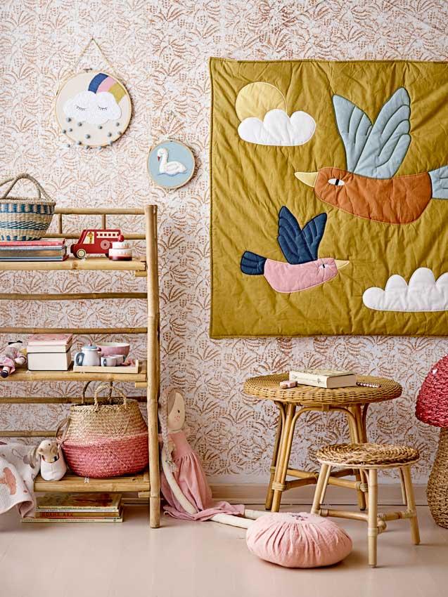 Rincón de juegos con estantes, mesa y taburete y panel textil en la pared