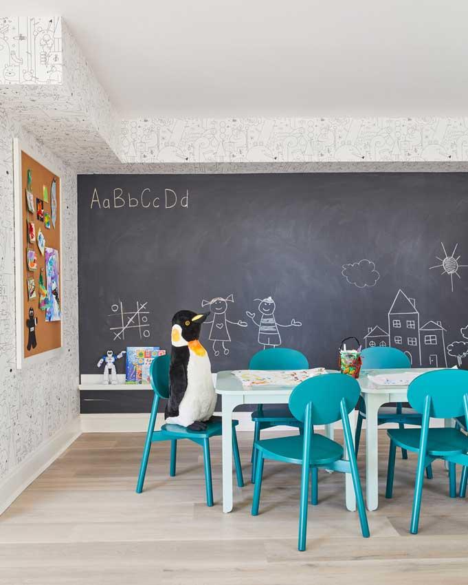 Cuarto de juegos con pizarra en la pared y mesa y sillas pequeñas