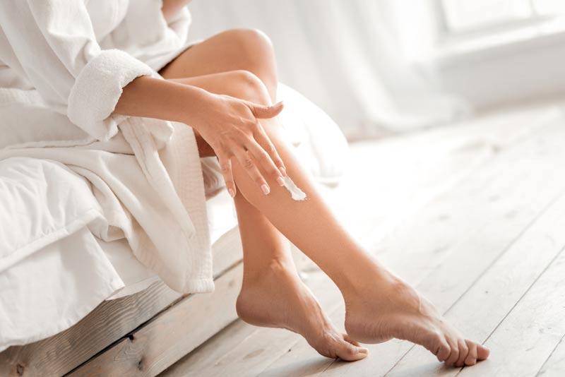 mujer aplicando crema corporal