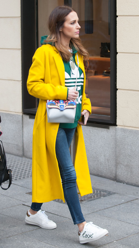 Lleva un abrigo amarillo y largo