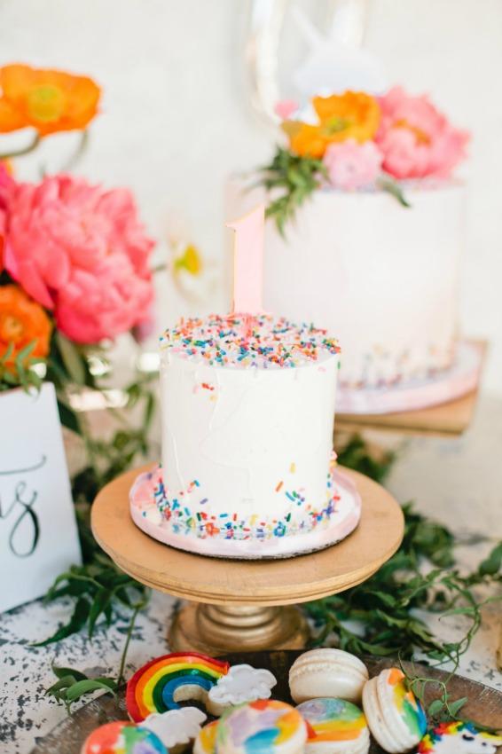 umixu de pasteles con frosting blanco y pepitas de colores y cake toppers de flores naturales