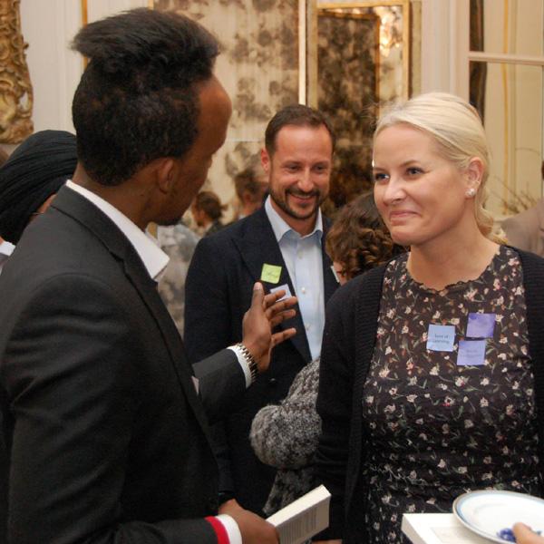 Haakon y Mette-Marit de Noruega debaten con varios ciudadanos en el salón de su casa