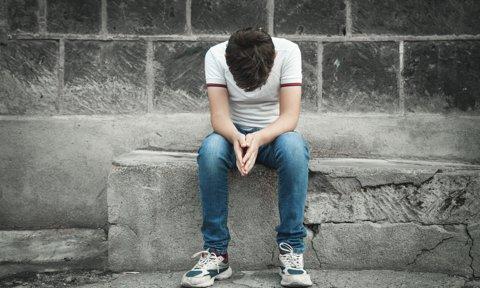 Adolescente con gesto cabizbajo sentado en la calle