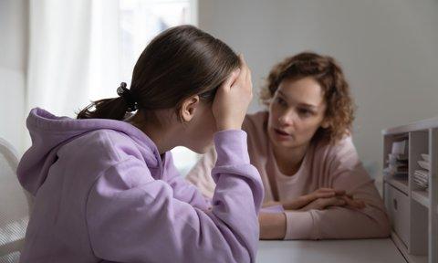 Madre hablando con su hija adolescente abatida
