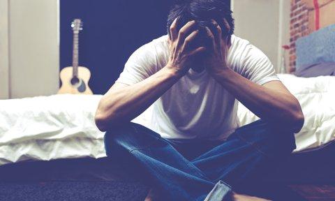 Adolescente sentado en el suelo con las manos en la cara