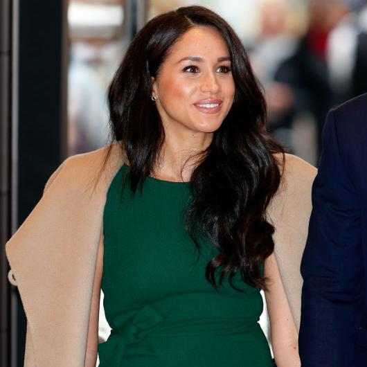 Meghan Markle with a green dress, hair down, and radiant skin
