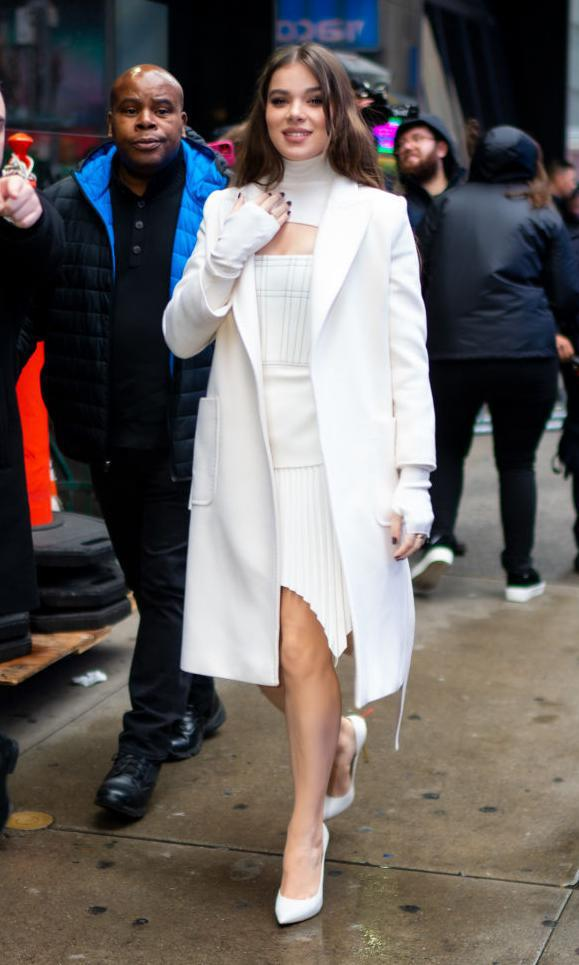 Hailee Steinfeld con white long coat, knit dress y pumps