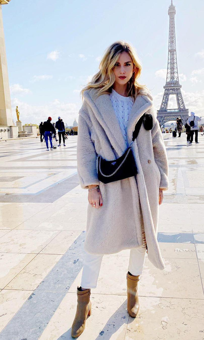 Chiara Ferragni con beige long coat, white sweater, white pants y ankle boots