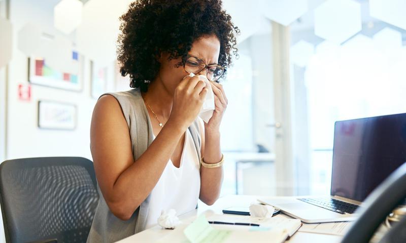 Mujer afrodescendiente tapándose la boca con un pañuelo al estornudar