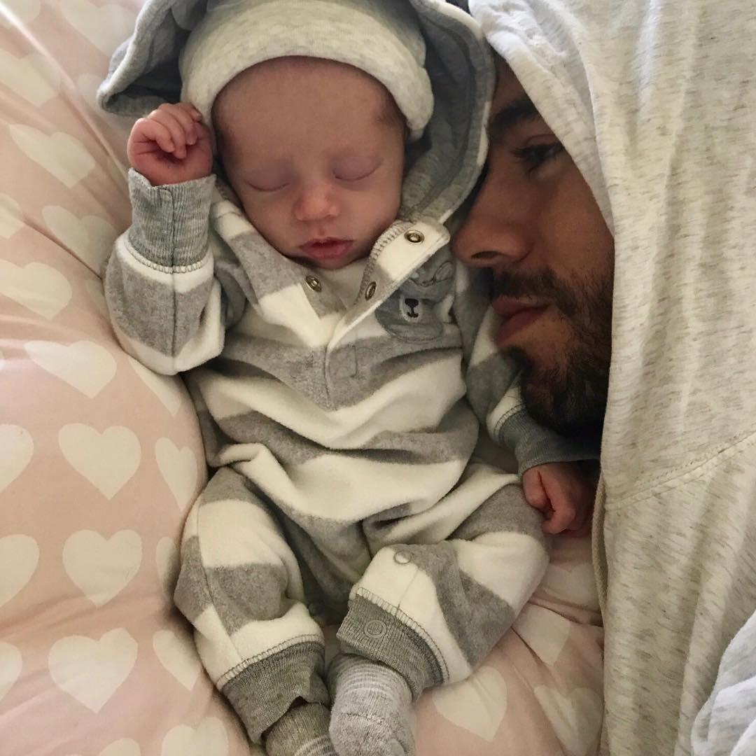Enrique Iglesias posing with newborn baby