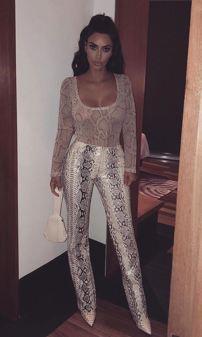 Kim Kardashian in a sheer snakeskin print top with tonal pants and pointed boots