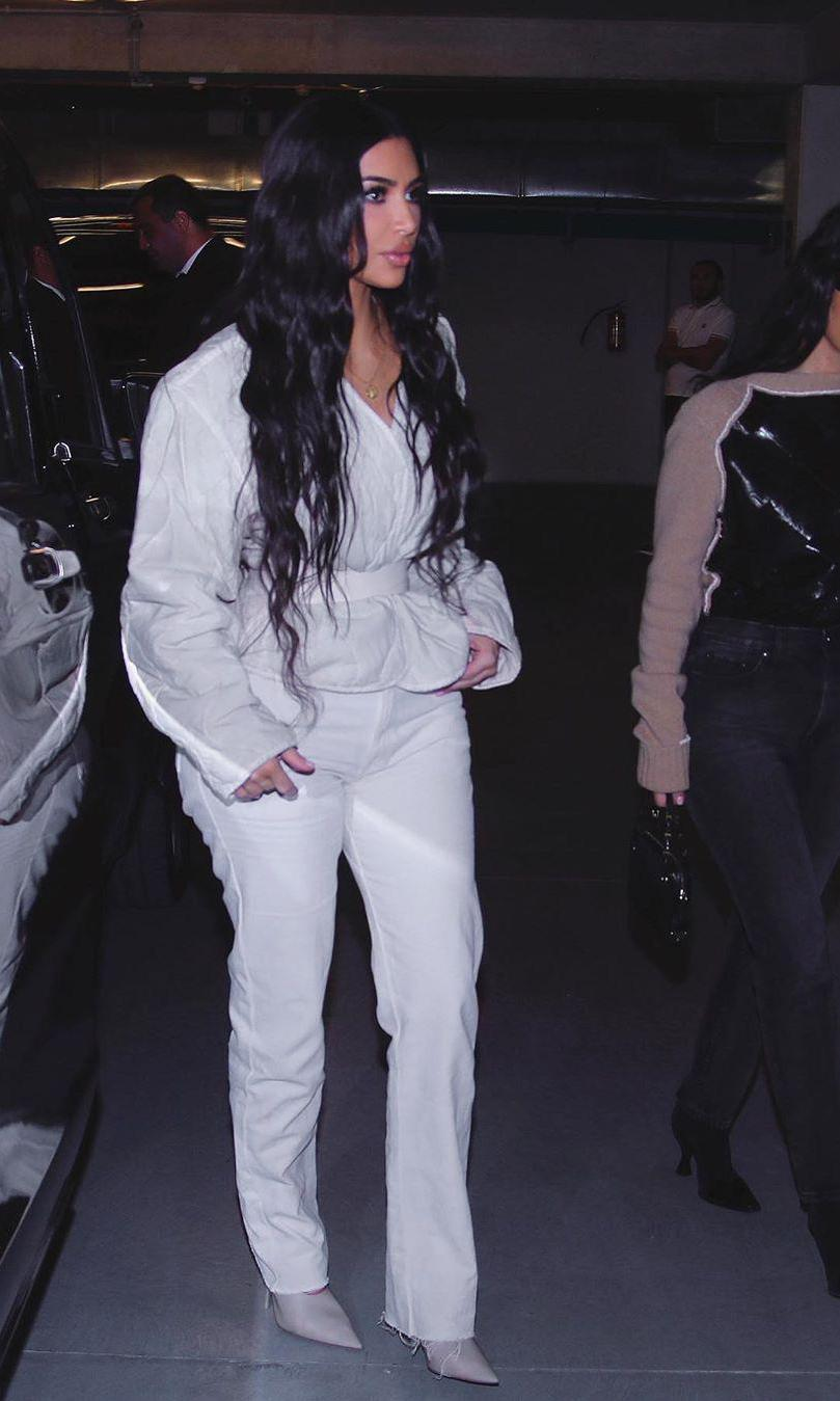 Kim Kardashian in an all-white jacket, pants, and boots