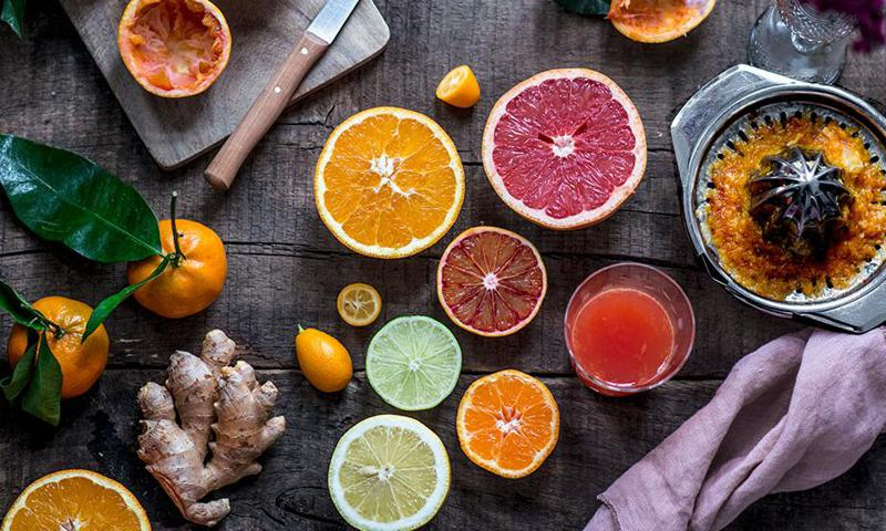 Orange, blood orange, grapefruit, lime, lemon, clementine, kumquat and ginger with a glass of juice and a citrus press