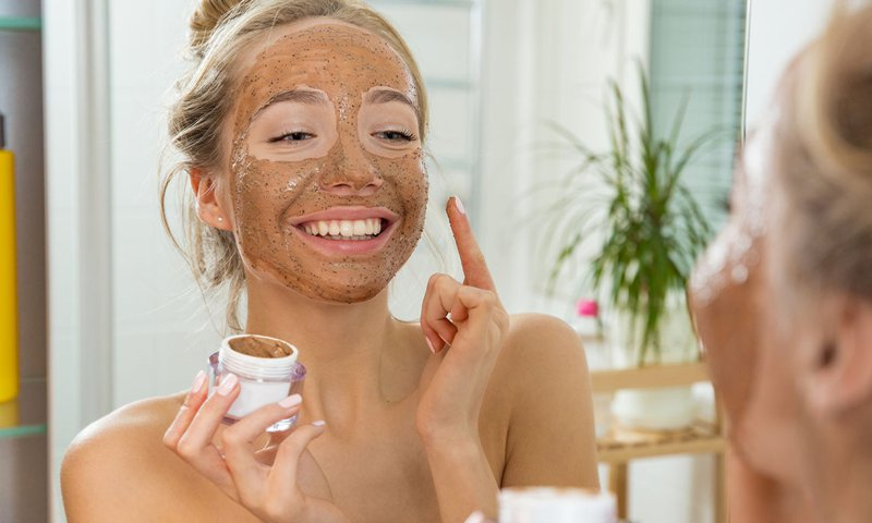 Woman applying an exfoliating mask