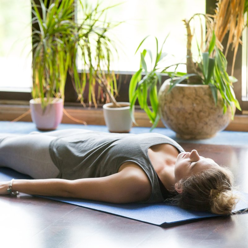 Mujer realiza Yoga sobre mat posición Savasana